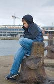 Infeliz menino sentado junto a água em uma porta, chuva — Foto Stock