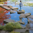 Little by in a stipy jumper is walking on the stepping stones - Stock Photo