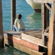 Little boy sitting in the sun on a wooden pier in Venice; Italy — Stock Photo