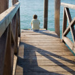 Stock Photo: Little boy sitting in the sun on a wooden pier in Venice; Italy