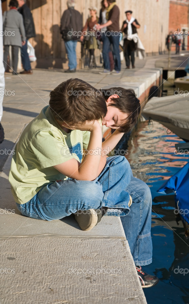 Two brothers resting at a canal edge on Murano in lagoon of Venice — Stock Photo #7842366
