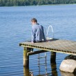 Northern summer - middle age man sitting on an old wooden pier; — Stock Photo