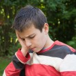Stock Photo: Thoughtful pre-teen boy outdoors
