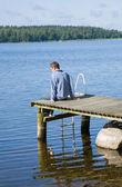 Verano del hemisferio norte - hombre de mediana edad sentado en un antiguo muelle de madera; — Foto de Stock