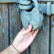 Old door locked with girl's hand — Stockfoto