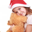 Santa's hat, little girl and a fluffy toy — Stock Photo