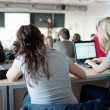 Young pretty female college student sitting in a classroom full — Stock Photo #7415818
