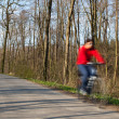 Bikers on a biking path in a park (motion blur is used to convey — Stock Photo