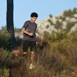 Stock Photo: Runner moving through sunlit landscape