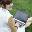 Pretty young woman working on a laptop computer outdoors, lookin — Stock Photo
