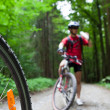 Stock Photo: Mountain biking in a forest - bikers on a forest biking trail (s