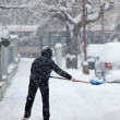 Woman shoveling snow from a sidewalk after a heavy snowfall in a - Stock Photo