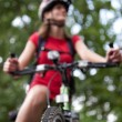 Pretty young female biker outddors on her mountain bike (shallow — Stock Photo #7416585