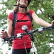Pretty young female biker outddors on her mountain bike (shallow — Stock Photo