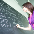 Pretty young college student writing on the chalkboard - Stock Photo
