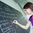Pretty young college student writing on the chalkboard — Stock Photo #7416865