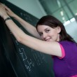 Pretty young college student writing on the chalkboard/blackboar — Stock Photo #7416935