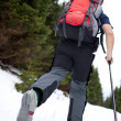 Young man cross-country skiing on a snowy forest trail — Stock Photo