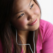 Young woman listening to music, smiling — Stock Photo #7417326