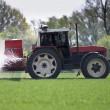 Tractor spraying a filed with pesticides/fertilizers — Stock Photo #7417327