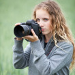 Pretty young woman with a DSLR camera outdoors taking pictures — Stock Photo #7417650