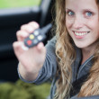 Pretty young woman showing off her brand new car - showing you t — Stock Photo