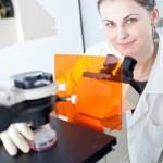Pretty female researcher using a microscope in a lab — Stock Photo #7417963