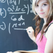 Pretty young college student writing on the chalkboard — Stock Photo #7418674