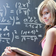 Pretty young college student writing on the chalkboard — Stock Photo