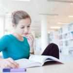 ganska unga collegestudent i ett bibliotek — Stockfoto