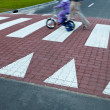 Father with a small girl on a bike crossing a street (motion bl — Zdjęcie stockowe