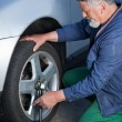 Mechanic changing a wheel of a modern car - Stockfoto