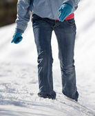 Pretty young woman walking in deep snow on a sunny winter day — Stock Photo