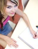 Portrait of a pretty young college student in a classroom — Stock Photo