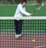 Tennis player in action (selective focus, focus on the net) — Stock Photo