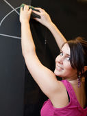 Pretty young college student drawing on the chalkboard — Stock Photo