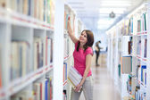 Pretty young college student in an university library — Stock Photo