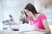 In the library - pretty female student with laptop and books — Stockfoto