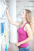 Pretty female college student in a llibrary looking for a book — Stock Photo