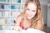 Pretty female college student in a library — Foto de Stock