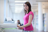 Pretty young woman using a copy machine — Stock Photo