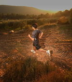 Runner moving through sunlit landscape. — Stock Photo