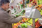 Handsome senior man shopping for fresh fruit in a supermarket — Stock Photo