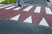 Father with a small girl on a bike crossing a street (motion bl — Stock Photo