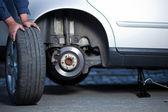 Mecánico cambiando una rueda de un coche moderno — Foto de Stock