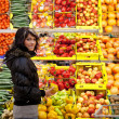 Beautiful young woman buying fruits and vegetables at a produce - Zdjcie stockowe