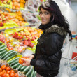 Beautiful young woman buying fruits and vegetables at a produce — Stock Photo