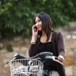 Young woman on a bicycle outdoors smiling — Stock Photo