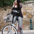 Young woman on a bicycle outdoors smiling — Stock Photo #7420177