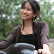 Young woman on a bicycle outdoors smiling — Stock Photo #7420183